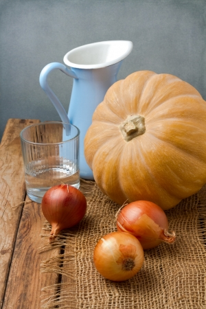 Still life with pumpkin and onions on wooden table Stock Photo - 21736231