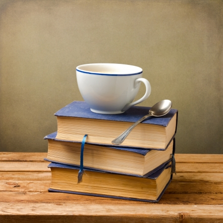 Old books and cup of coffee on wooden table over grunge background photo