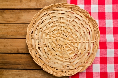Wicker plate on checked tablecloth over wooden background photo