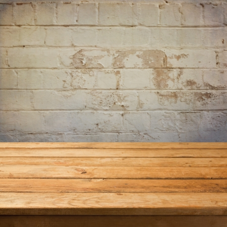 Empty wooden deck table over grunge stone wall