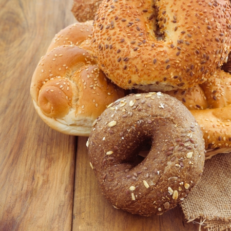 Freshly baked bread and buns on wooden background photo