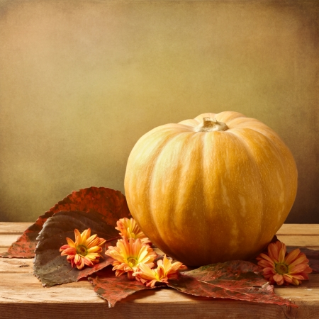 Pumpkin with autumn leaves and flowers on wooden table over grunge background