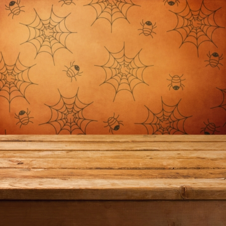 Halloween holiday background with empty wooden table and wallpaper with spiders Stock Photo