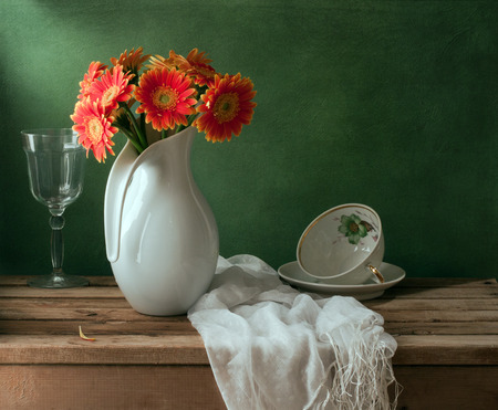 arrangment: Still life with orange gerbera daisy flower and empty cup Stock Photo