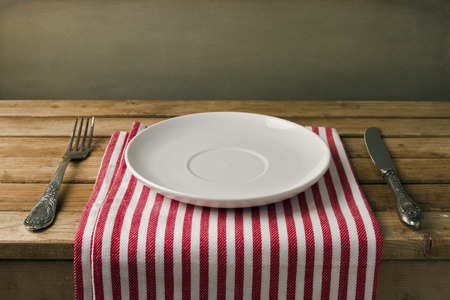 fine wood: Empty plate with fork and knife on wooden table. Table arrangement.