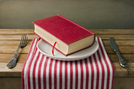 wooden plate: Book on plate with knife and fork. Table arrangement. Stock Photo