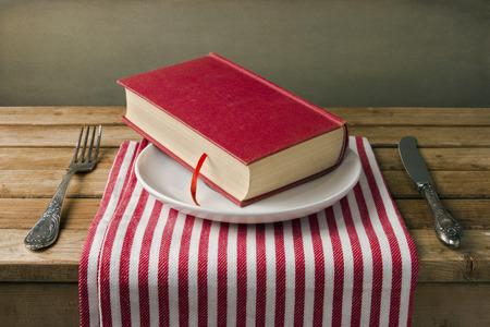 libros antiguos: Libro en el plato con cuchillo y tenedor. Disposición de la tabla.