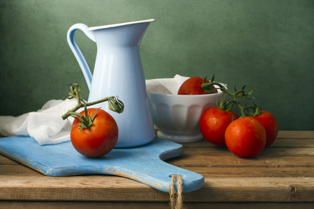 tableware life: Still life with tomatoes and enamel jug. Arrangement on wooden table.