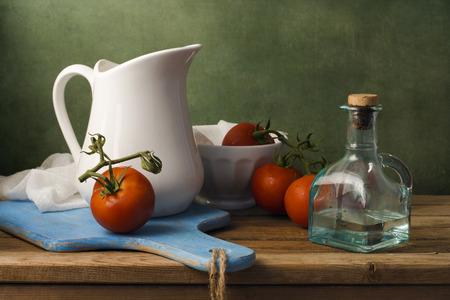トマトと白い水差しのある静物。木製のテーブルを配置。 写真素材