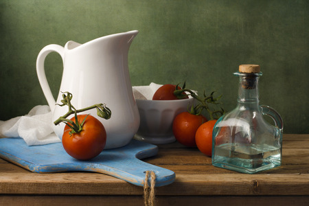 Still life with tomatoes and white jug. Arrangement on wooden table.