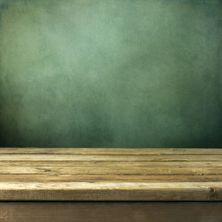 background cover: Wooden deck table on green grunge background Stock Photo