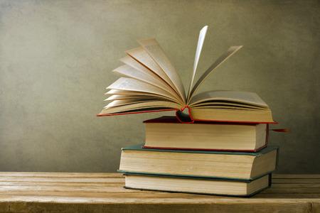 Vintage alte Bücher auf Holz-Deck Tisch und Grunge-Hintergrund