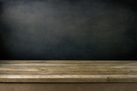 Background with grunge black wall and wooden table deck.