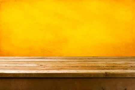 wood table: Fondo con el tablero de la mesa cubierta de madera y la pared del grunge amarillo