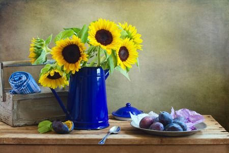 yellow tea pot: Still life with beautiful suflower bouquet on wooden tabletop against grunge wall Stock Photo