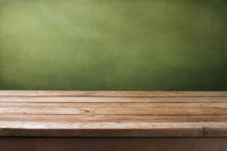 tabla de madera: Fondo con el tablero de la mesa cubierta de madera y el grunge pared verde Foto de archivo