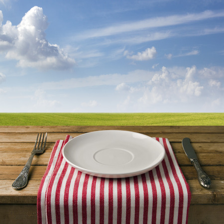 Empty plate with fork and knife on wooden table against blue sky and meadow. Table arrangement.