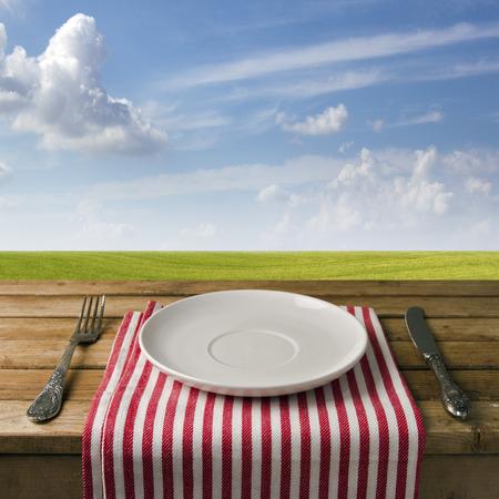 napkin: Plato vacío con tenedor y cuchillo en la mesa de madera contra el cielo azul y el prado. Disposición de la tabla.