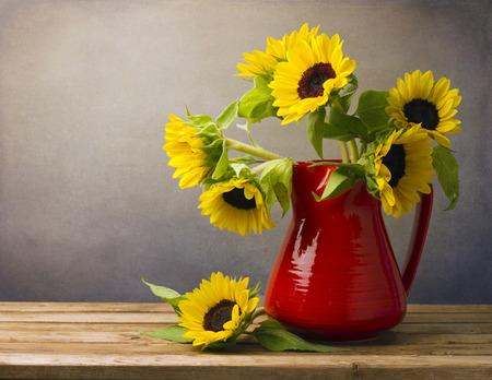木製のテーブルの上の赤い水差しの美しいヒマワリ花束。