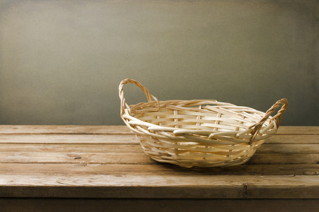empty basket: Background with wooden deck tabletop and empty basket against grunge wall