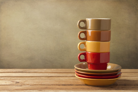Colorful coffee cups and plates on wooden table over grunge background