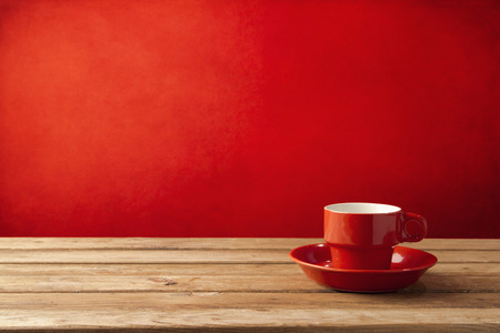 Red coffee cup on wooden table over red grunge background Foto de archivo