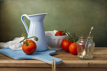 tableware life: Still life with fresh tomatoes and tableware on wooden table Stock Photo