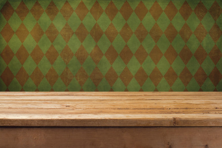 Vintage background with wooden table and grunge checked wall