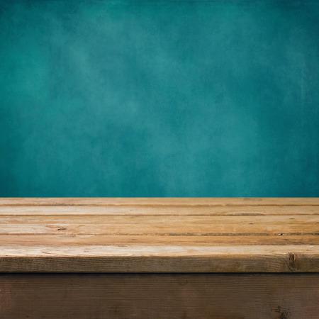 木製のテーブルとグランジの青い壁の背景