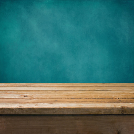 Background with wooden table and grunge blue wall Standard-Bild