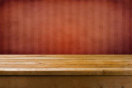 wood table: Fondo con mesa de madera y pared roja del grunge con tiras Foto de archivo