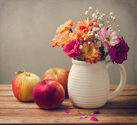 Beautiful flower bouquet and fresh apples on wooden tabletop Stock Photo