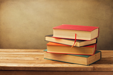 old book cover: Vintage old books on wooden deck tabletop against grunge wall Stock Photo