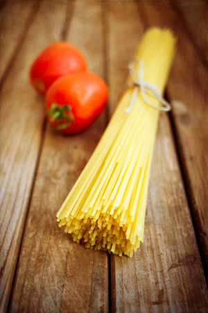 Pasta and tomatoes on vintage wooden table with grunge texture