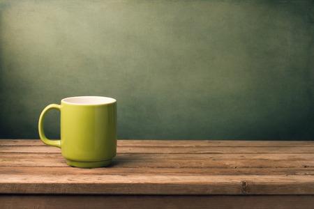 Green mug on wooden table over grunge background