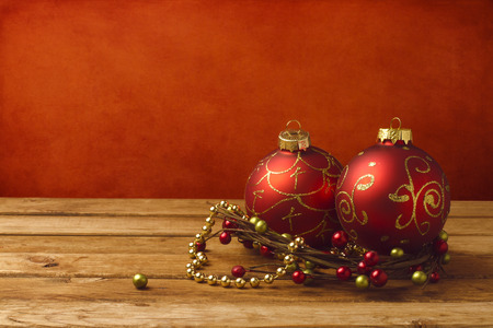 Christmas decoration on wooden table over red grunge background photo