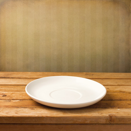 empty space: Empty white plate on wooden table over grunge striped wallpaper Stock Photo