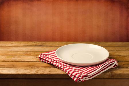 赤グランジ背景に木製のテーブルの空の白いプレート