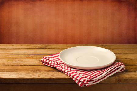 table wood: Empty white plate on wooden table over red grunge background