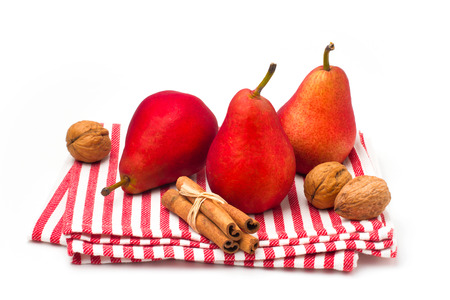 Red pears on striped tablecloth over white background