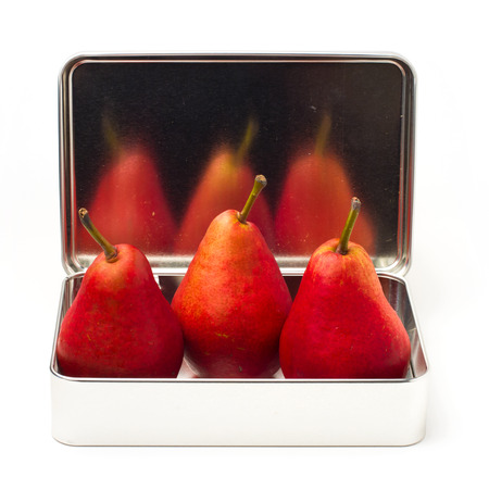 Three red pears in metal box reflecting in box cover over white background photo