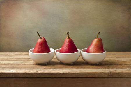 Fine art stilleven met rode peren op houten tafel Stockfoto