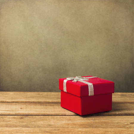 Red small gift box on wooden table over grunge background