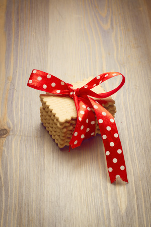 Cookies with ribbon on wooden tabletop