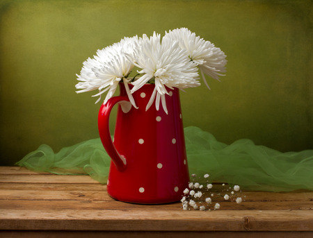 Still life with chrysanthemum flowers in red jug on wooden table over green grunge wall