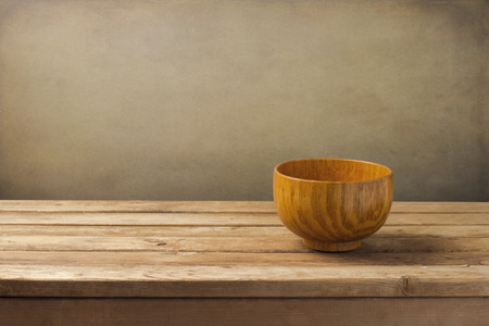 Empty wooden dish on table over grunge wall
