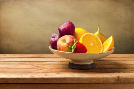 Vase with fresh fruits on wooden table