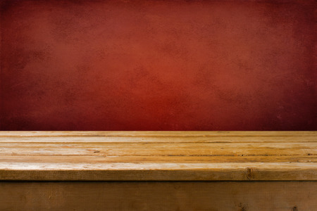 the red wall: Background with wooden table and red grunge wall