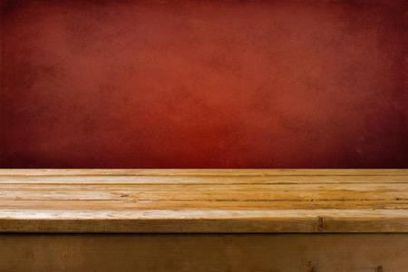 wood table: Fondo con mesa de madera y pared roja del grunge