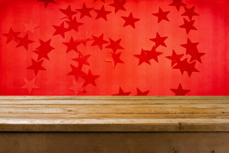 Background with wooden table and red grunge wall with stars Stock Photo